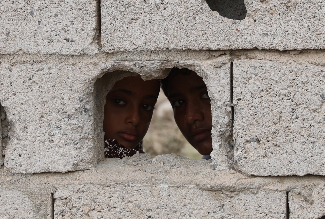 Children looking through shell hole - Al Munthar /Medium/